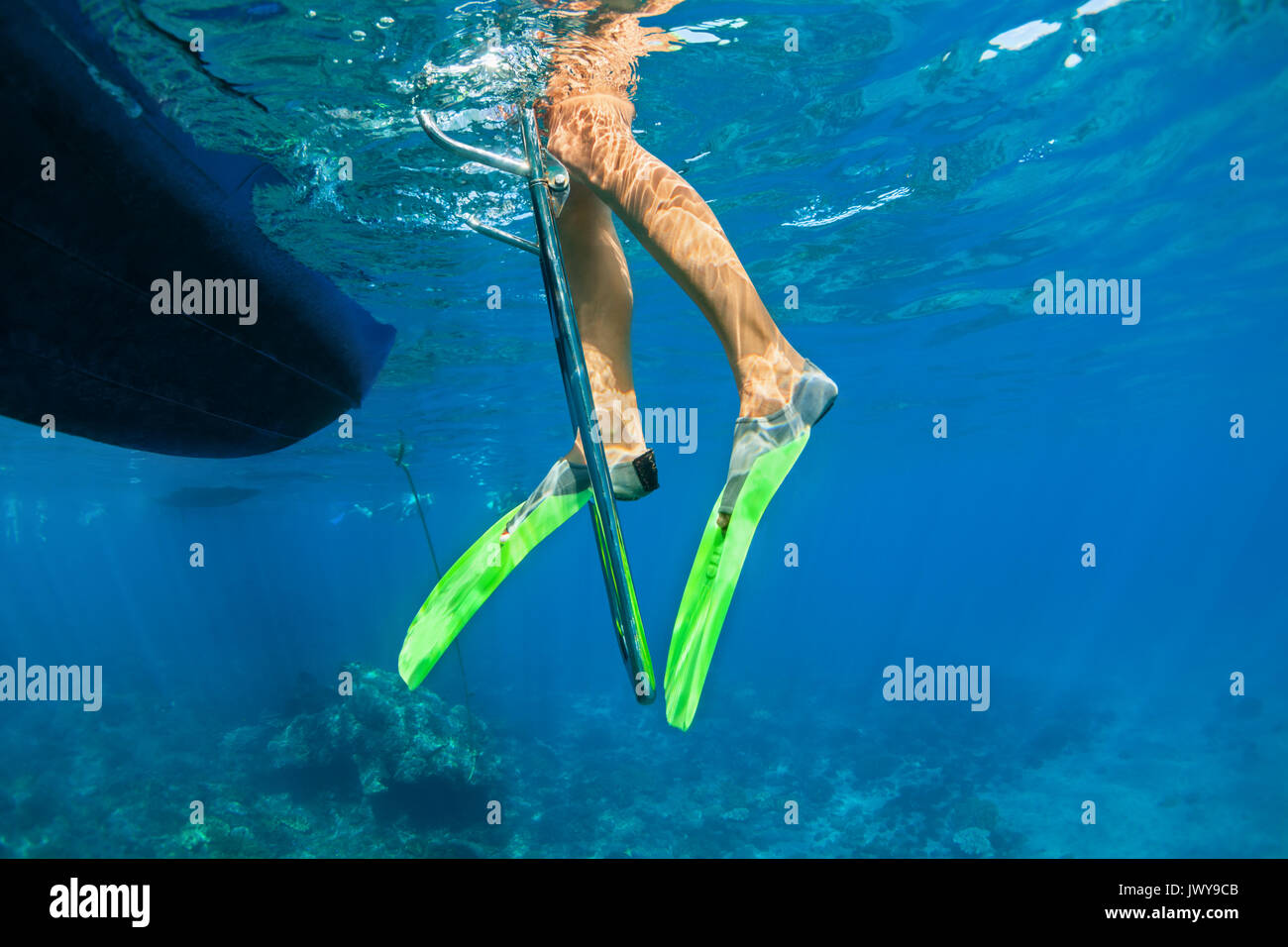 Child in snorkelling fins stand on divers boat ladder for diving underwater in tropical coral reef sea pool. Travel lifestyle, water sport adventure - Stock Image