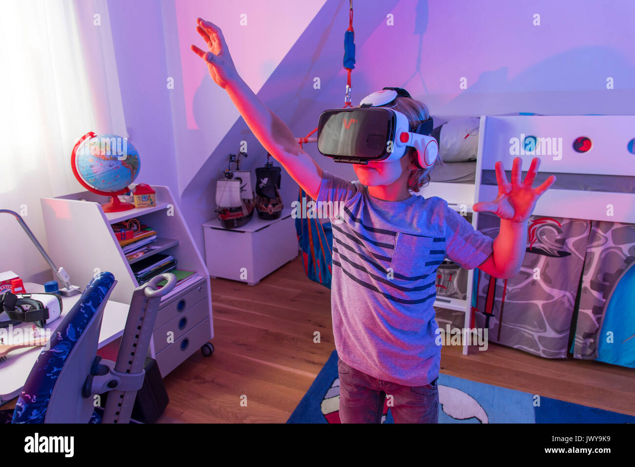 Little boy, 7 years old, plays a 3-D computer game, with a virtual reality headset, in his children's room, - Stock Image