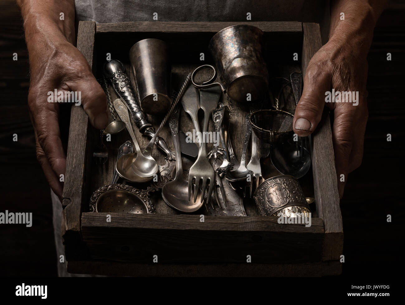 Man holding a wooden box with old silverware - Stock Image