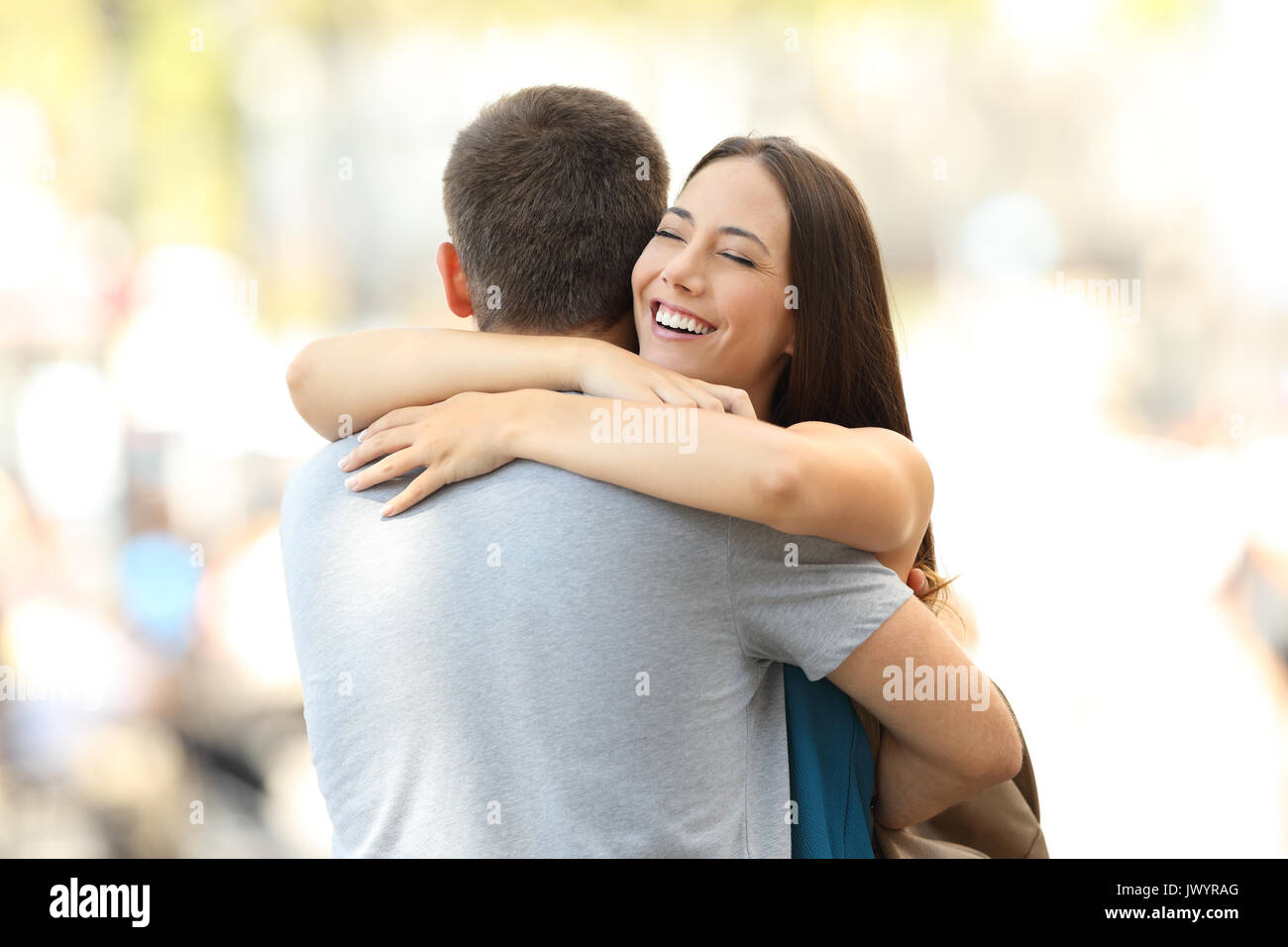 Happy girlfriend hugging her partner after encounter on the street - Stock Image