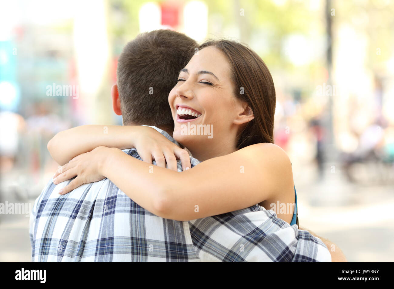 Happy couple or friends hugging after encounter on the street - Stock Image