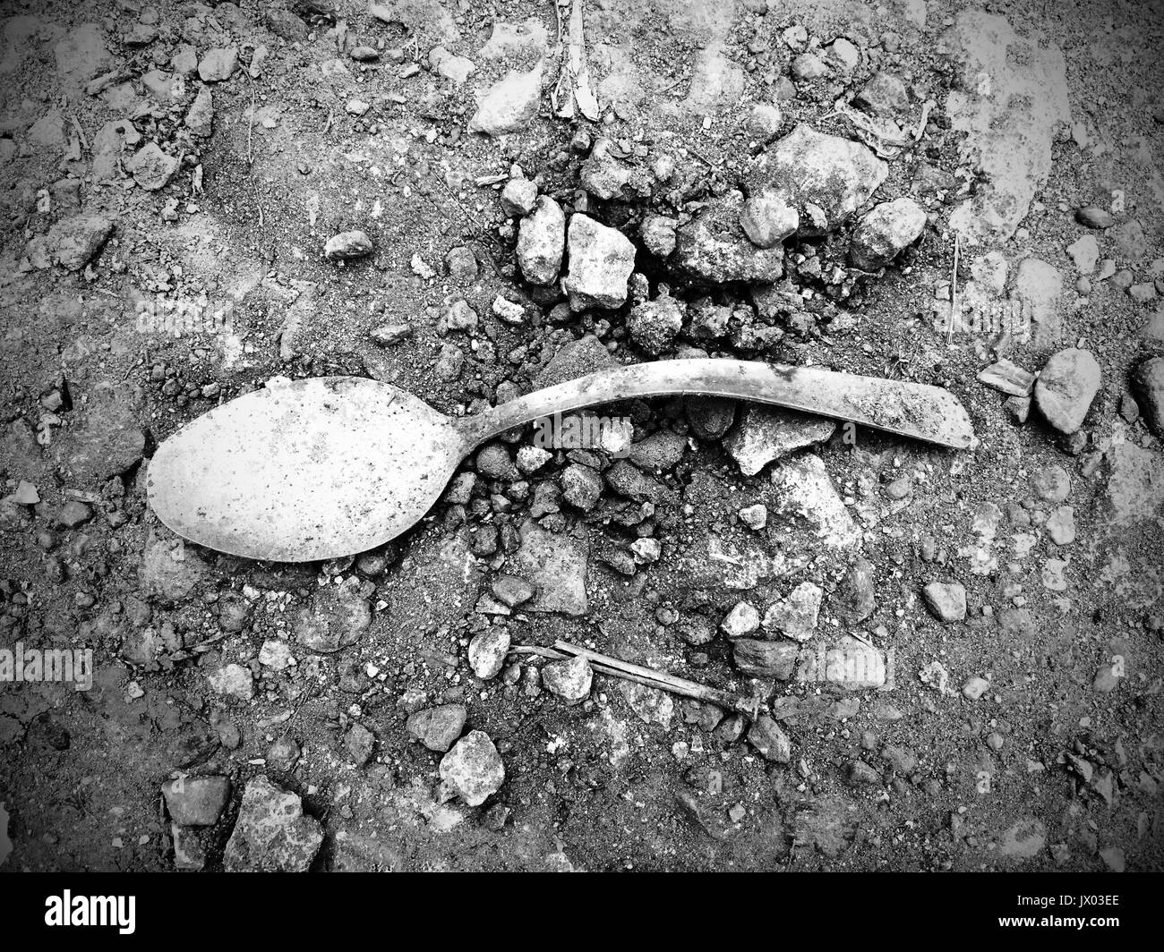 A distorted and dirty spoon in the ground is a fitting symbol of poverty in the Philippines. - Stock Image