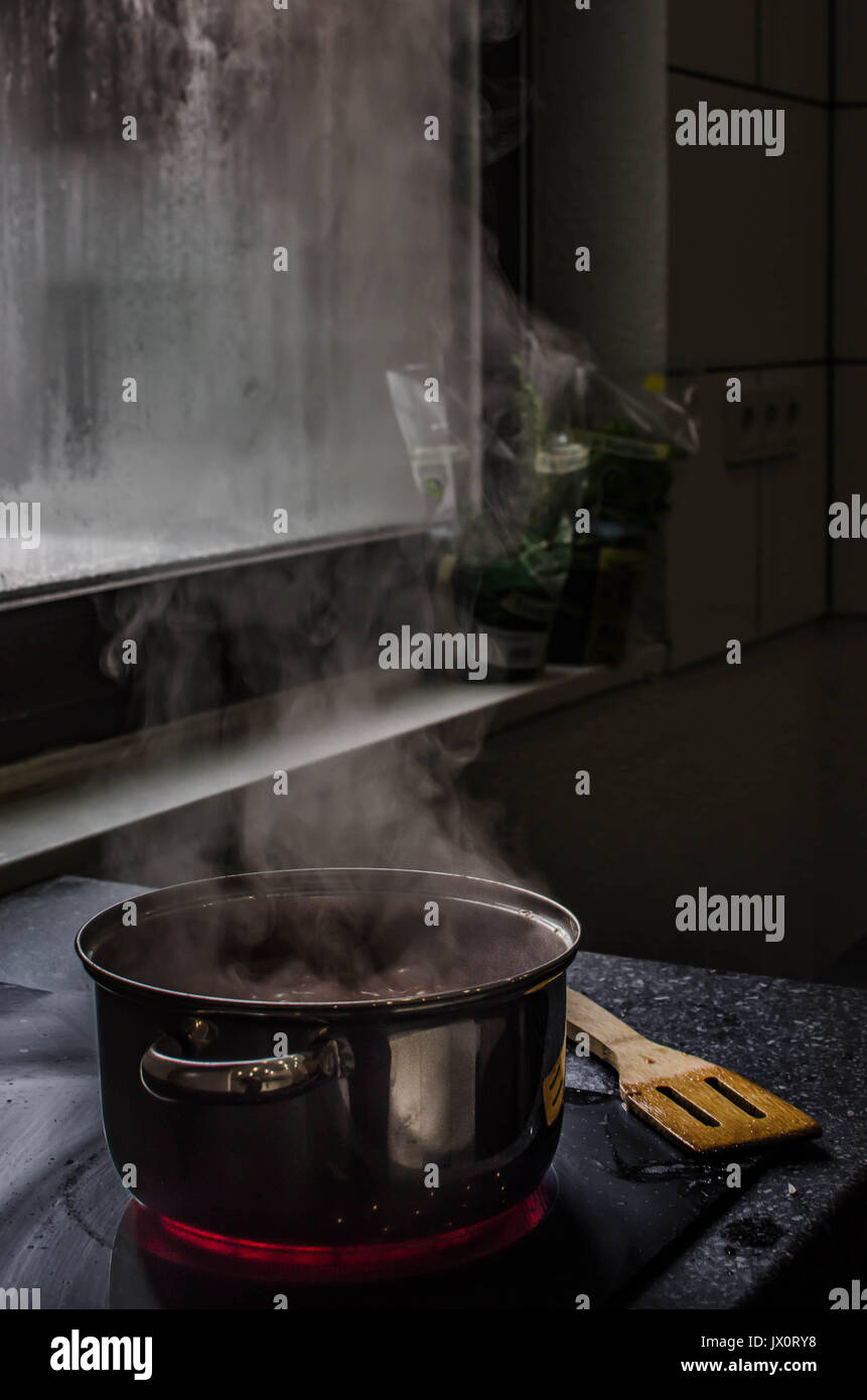 a simmering saucepan on a stove with fogged up windows in the background - Stock Image