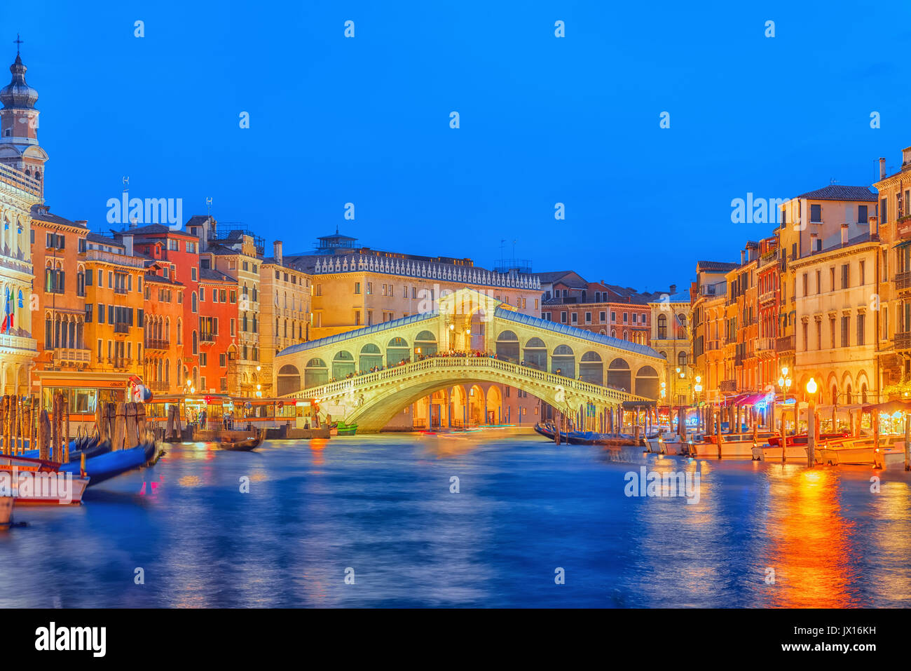 Rialto Bridge (Ponte di Rialto) or Bridge of Sighs and view of the most beautiful canal of Venice - Grand Canal and boats, gondolas, mansions along. N - Stock Image
