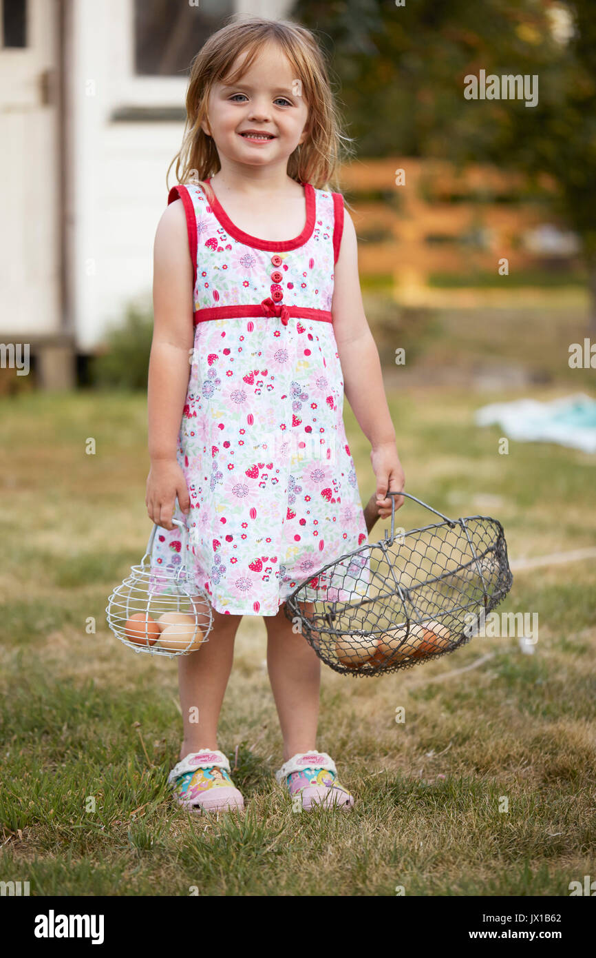 Little girl helping colect free range eggs with her egg basket. - Stock Image