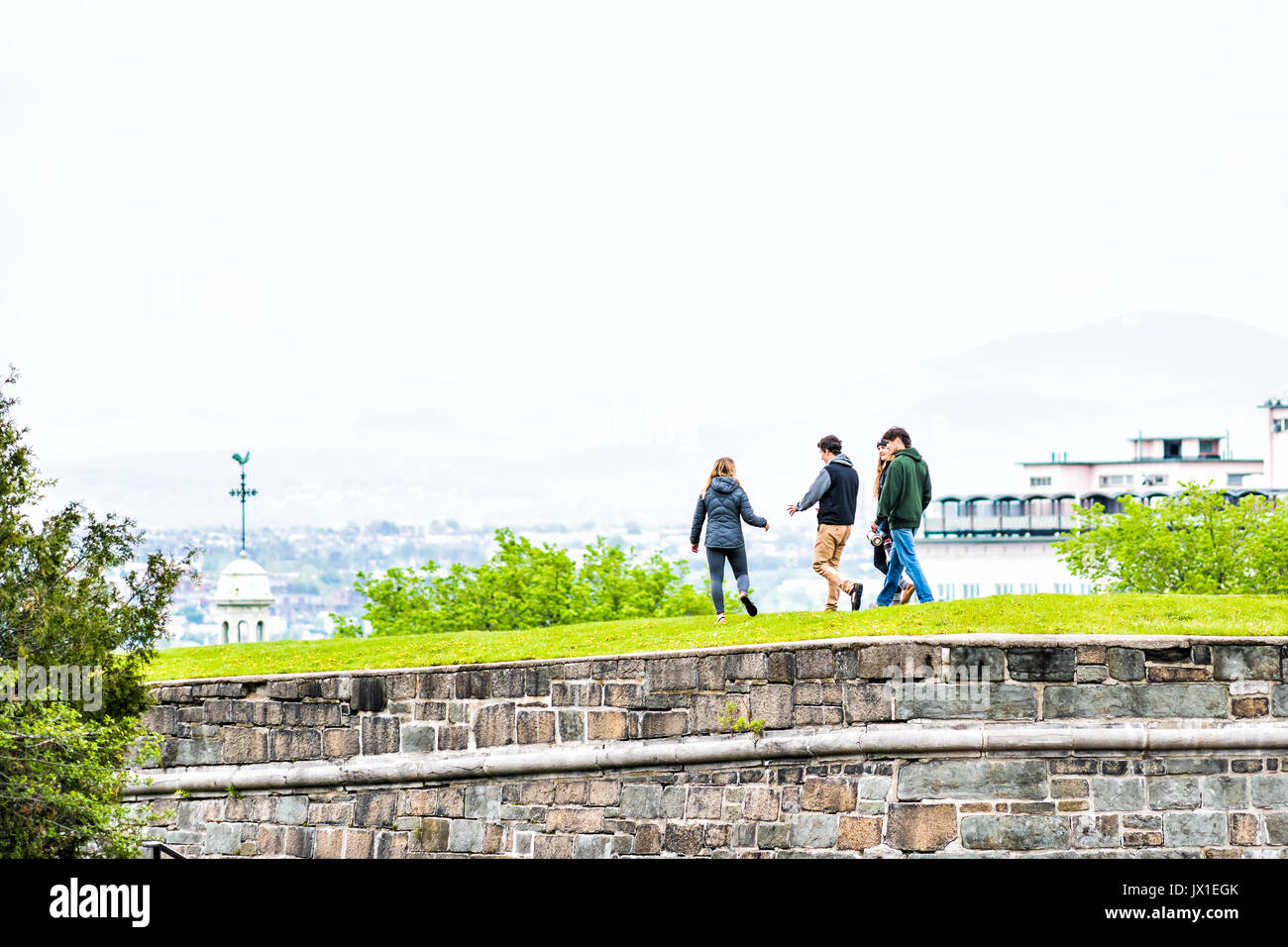 Quebec City, Canada - May 29, 2017: Group of young people walking on top of green grass fields in park with fortifications stone wall - Stock Image