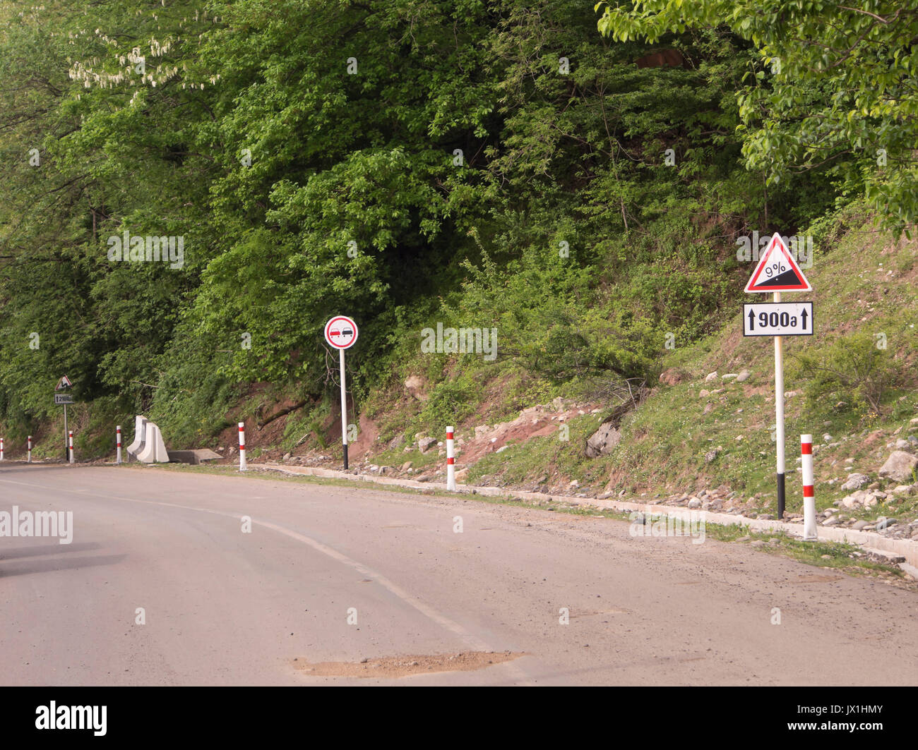 Sightseeing in Georgia can be challenging for the driver, road signs warning for 9 % steep decline near the Gelati monastery - Stock Image