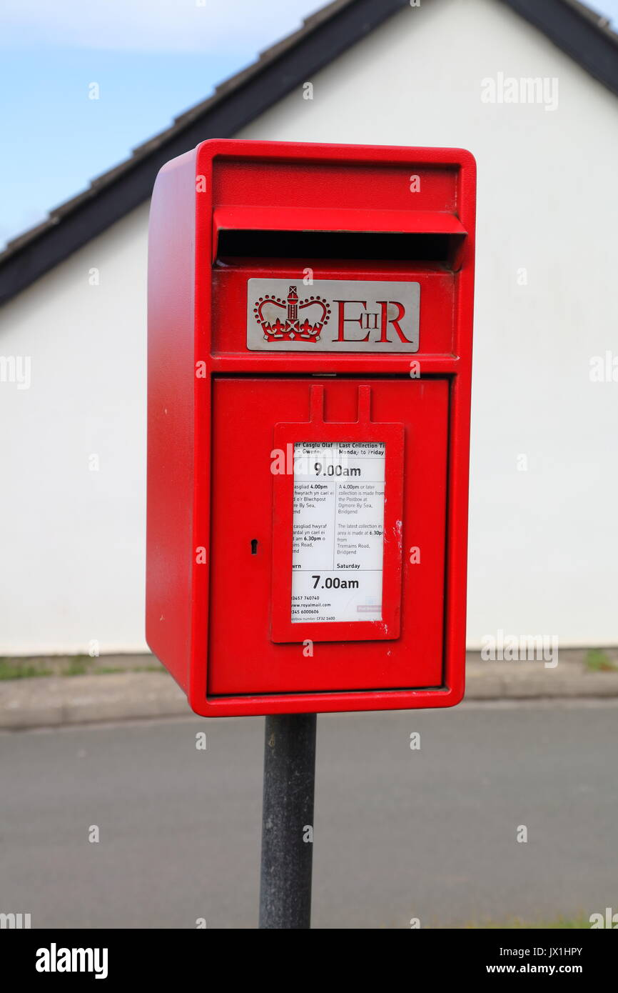 A fairly new post box besides the main road in a village with its usual red coat of paint and mounted on a post in the ground. - Stock Image