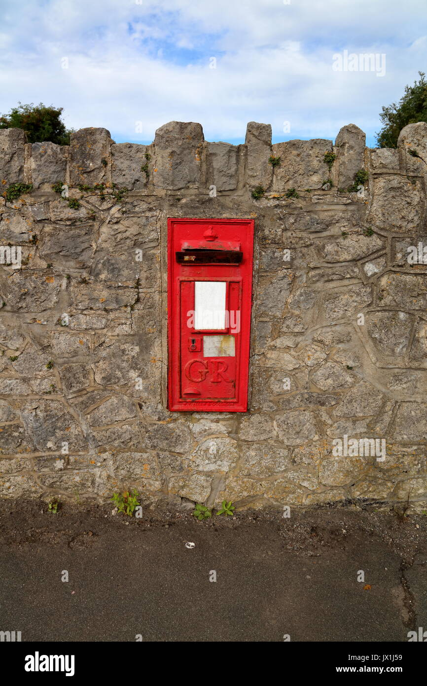 An old George Rex letter box situated in a wall along side the village main road, now blocked and disused with a Stock Photo