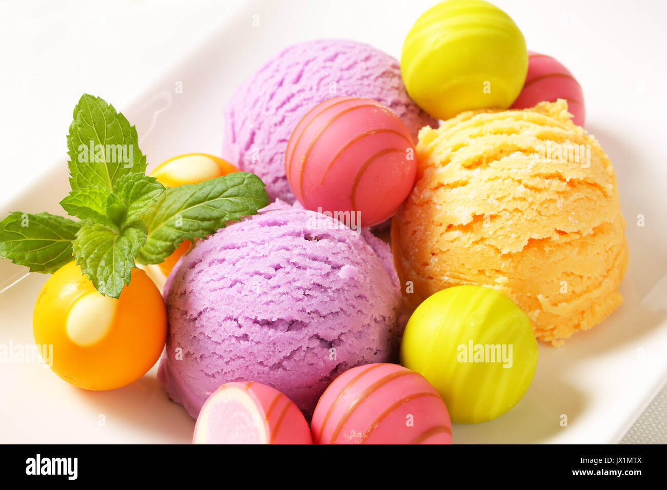 Fruit-flavored ice cream and white chocolate bonbons with fruit ganache filling Stock Photo
