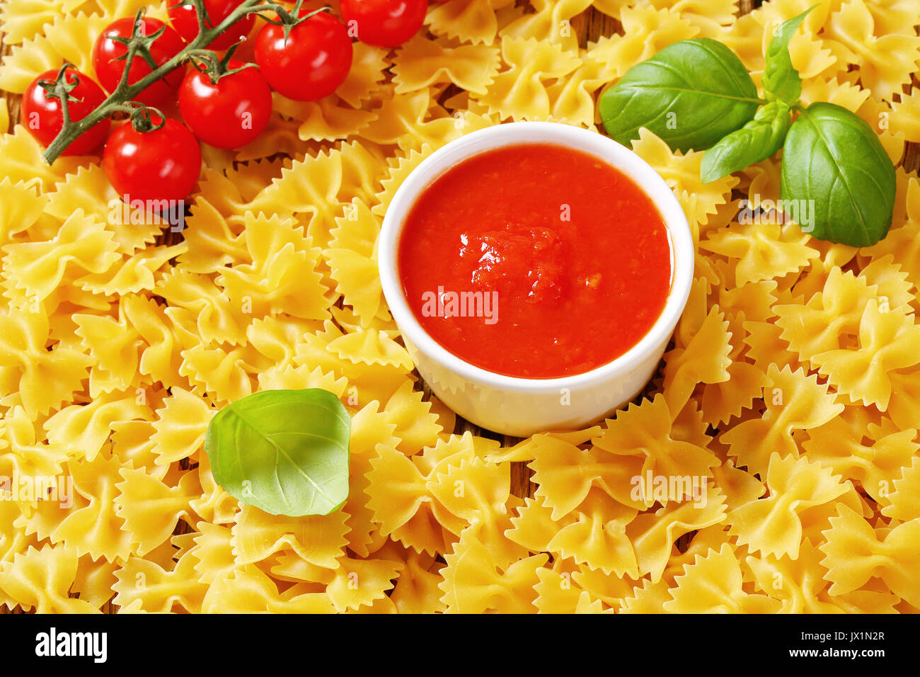 Uncooked bow tie pasta with tomato sauce - Stock Image