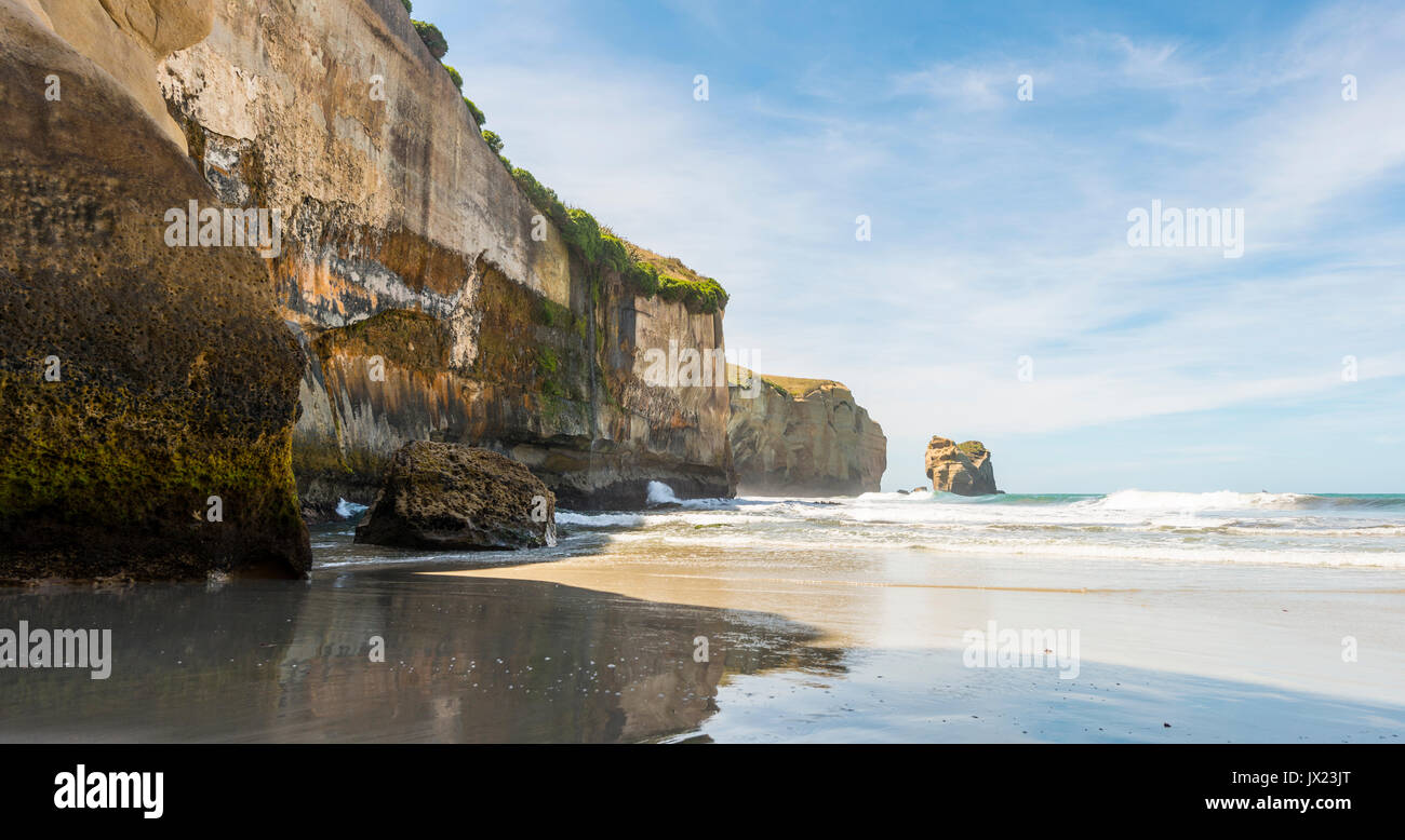 Sandstone rocks towering into the sea, Tunnel Beach, Otago, South Island, New Zealand - Stock Image