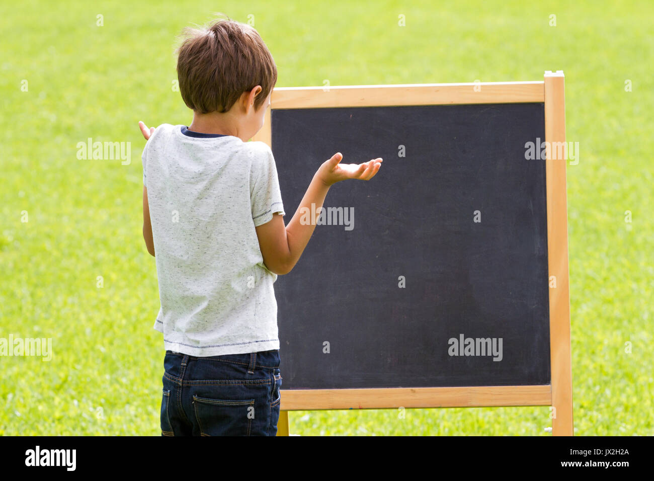 Thinking child by the blackboard outdoors - Stock Image