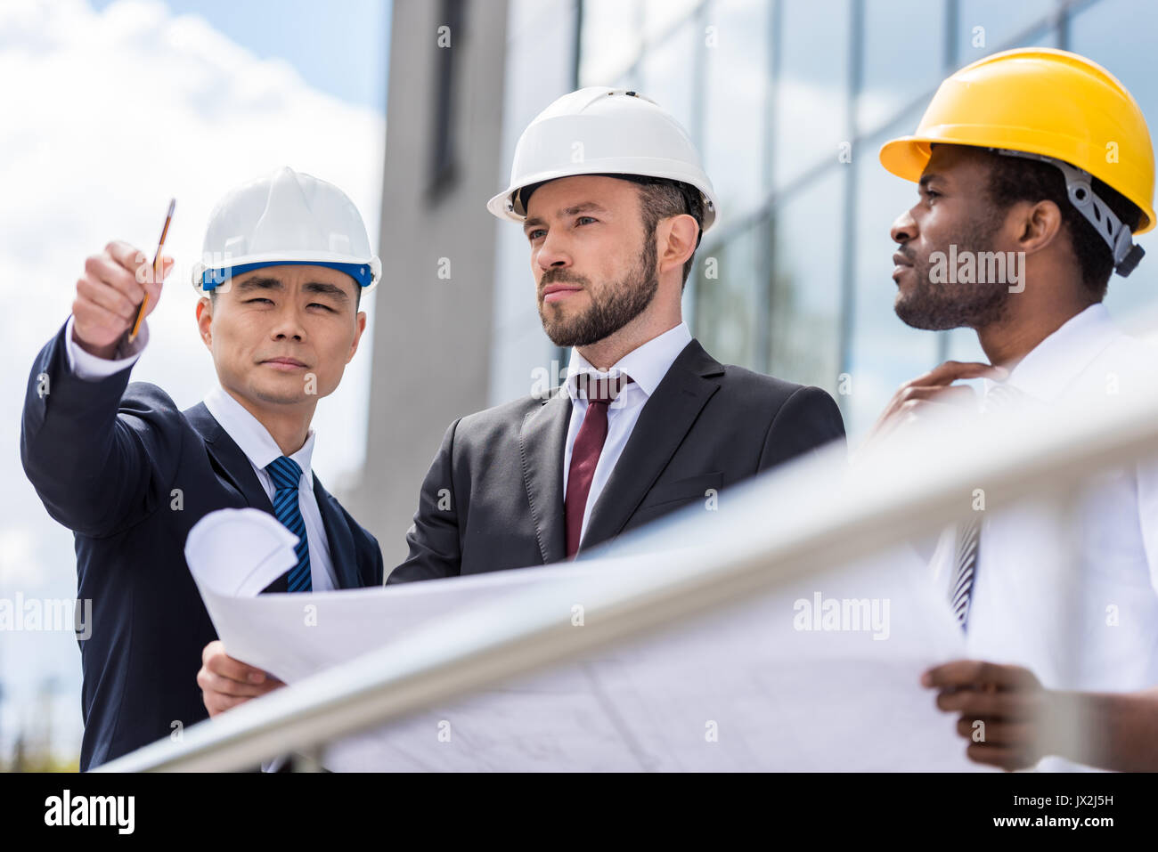 Professional architects in hardhats working with blueprint outside modern building - Stock Image