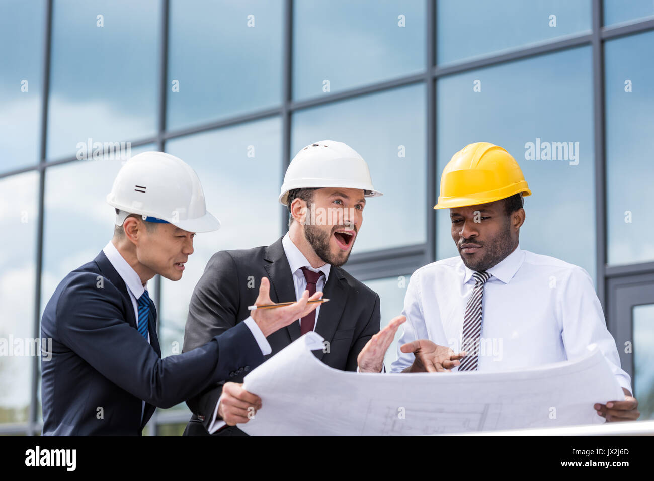 Group of professional architects in hardhats discussing blueprint outside modern building - Stock Image