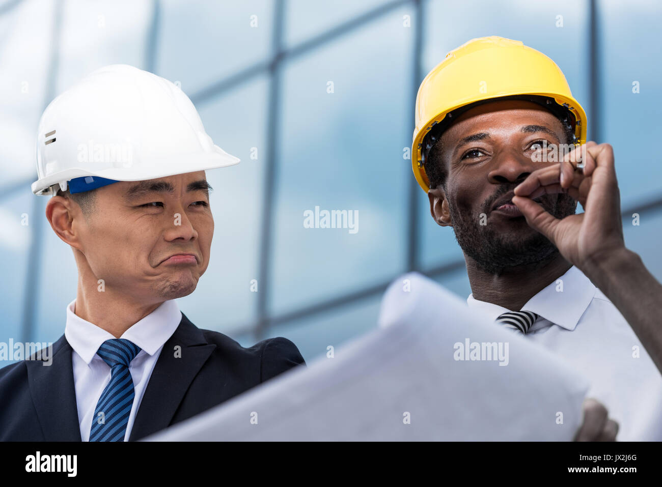 Close-up view of professional architects in hardhats working with blueprint - Stock Image