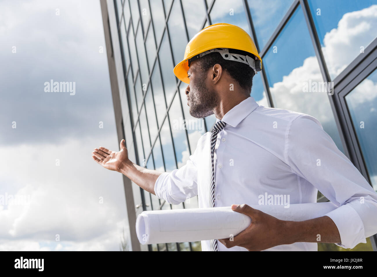 Low angle view of professional architect in hard hat holding blueprint outside modern building - Stock Image