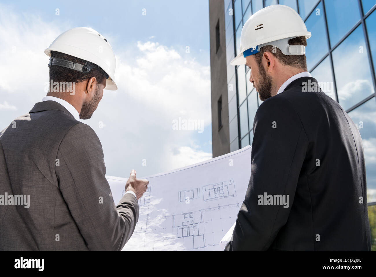 Back view of professional architects in hardhats working with blueprint - Stock Image