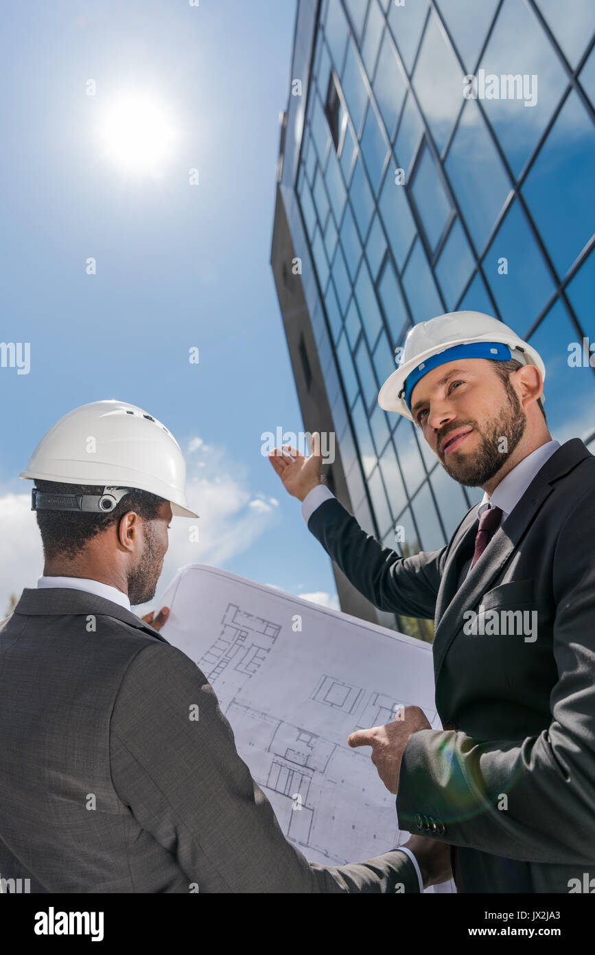 Low angle view of professional architects in hardhats working with blueprint - Stock Image