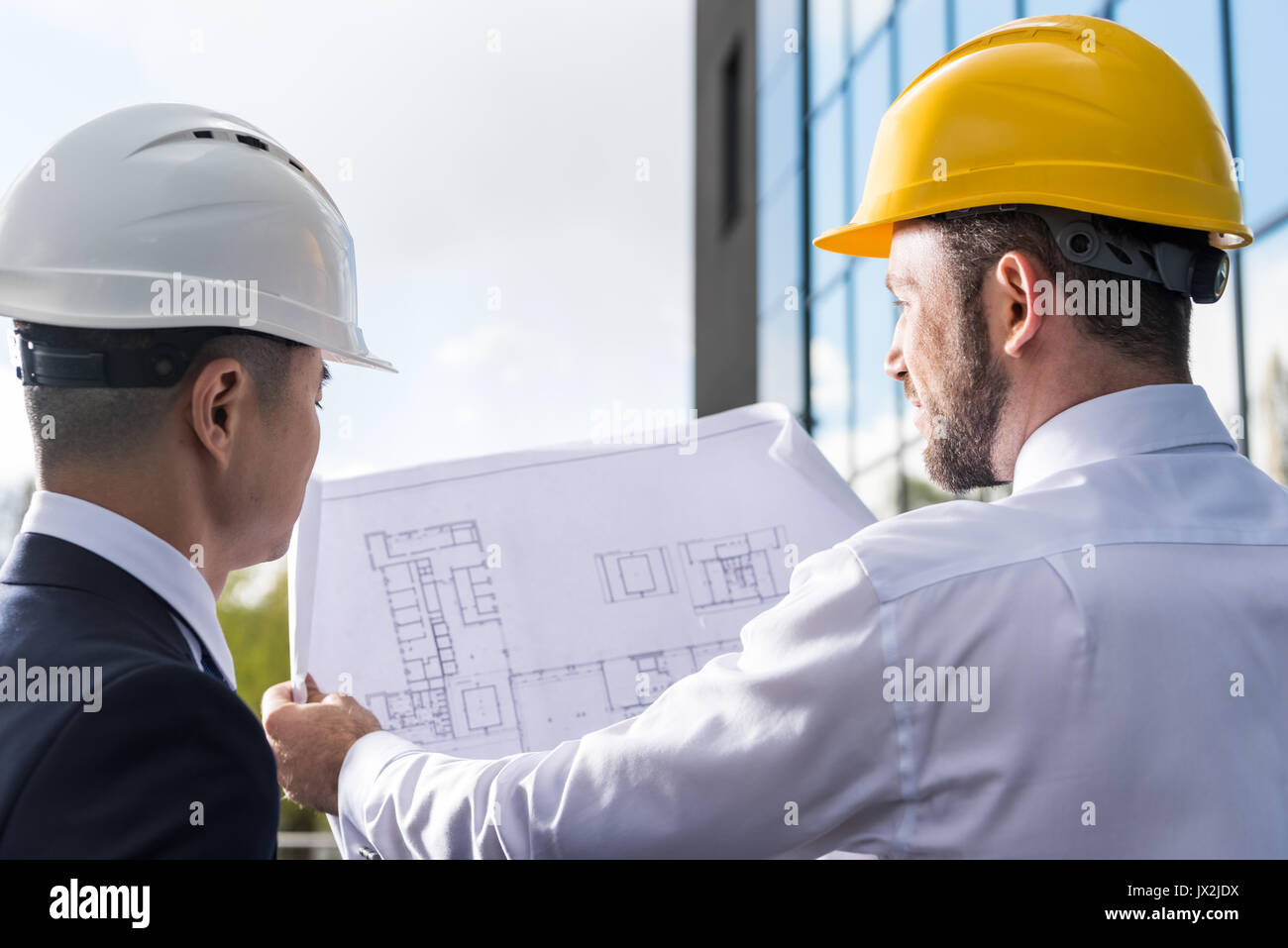 back view of professional architects in hard hats discussing project  - Stock Image