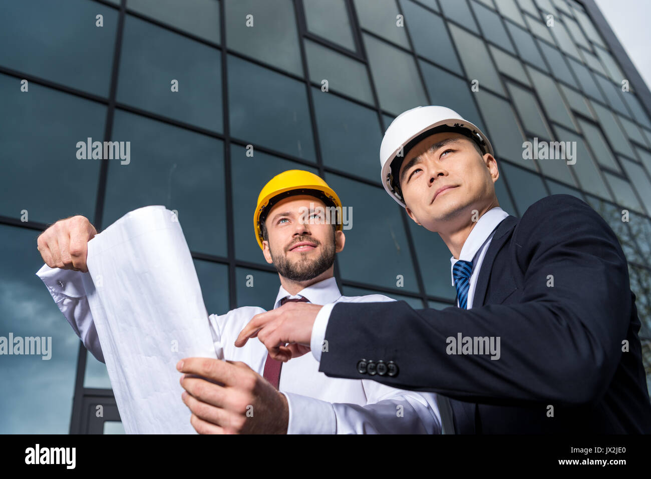 low angle view of professional architects in hard hats discussing project, successful businessmen concept  - Stock Image