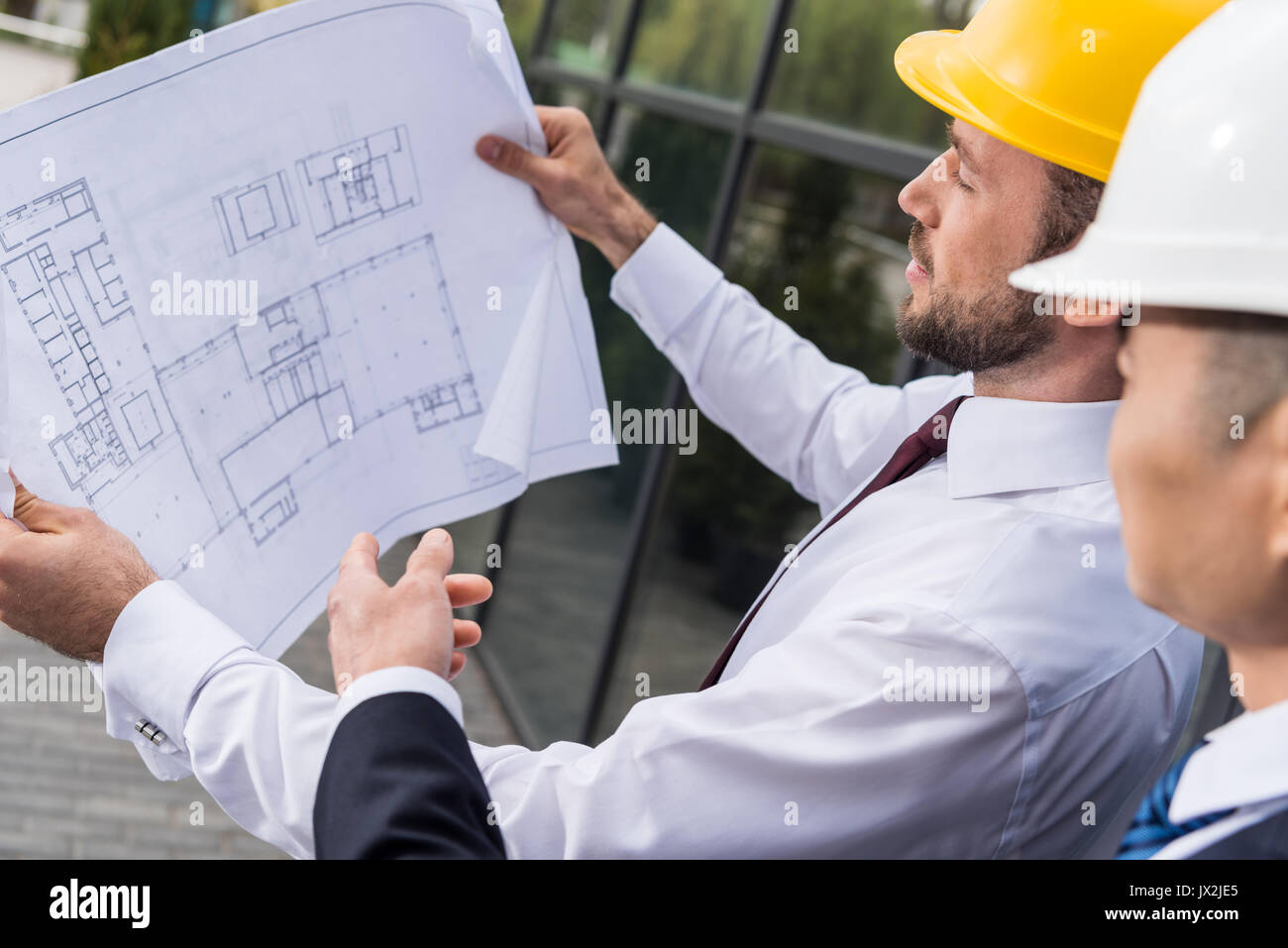 side view of professional architects in hard hats discussing project, successful businessmen concept  - Stock Image