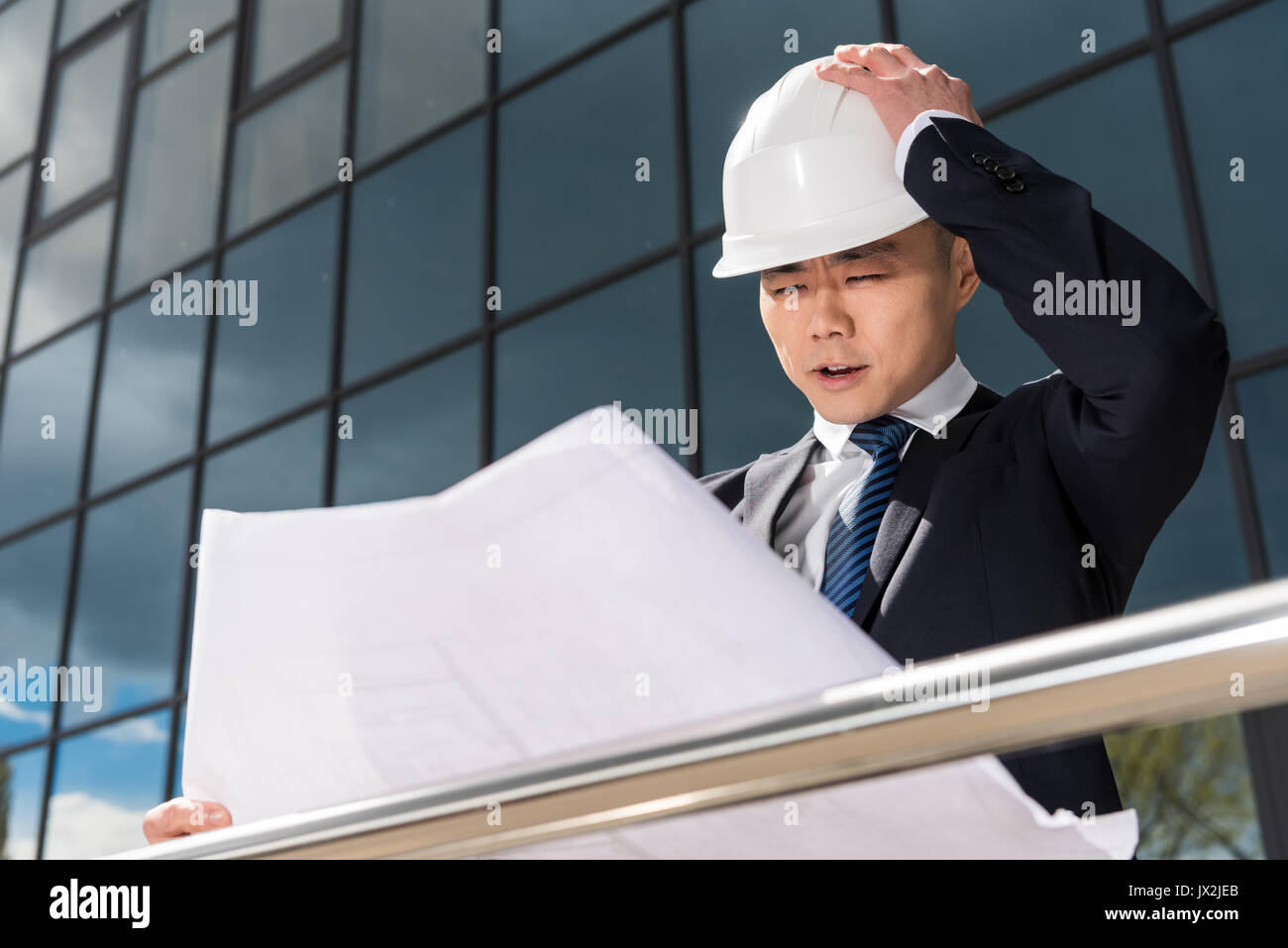 portrait of confused professional architect in hard hat looking at blueprint - Stock Image
