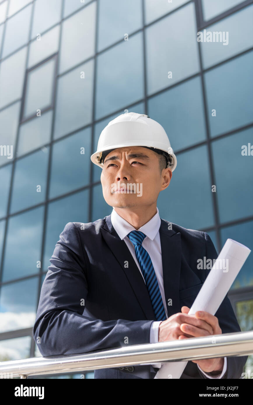 portrait of pensive professional architect in hard hat holding blueprint - Stock Image