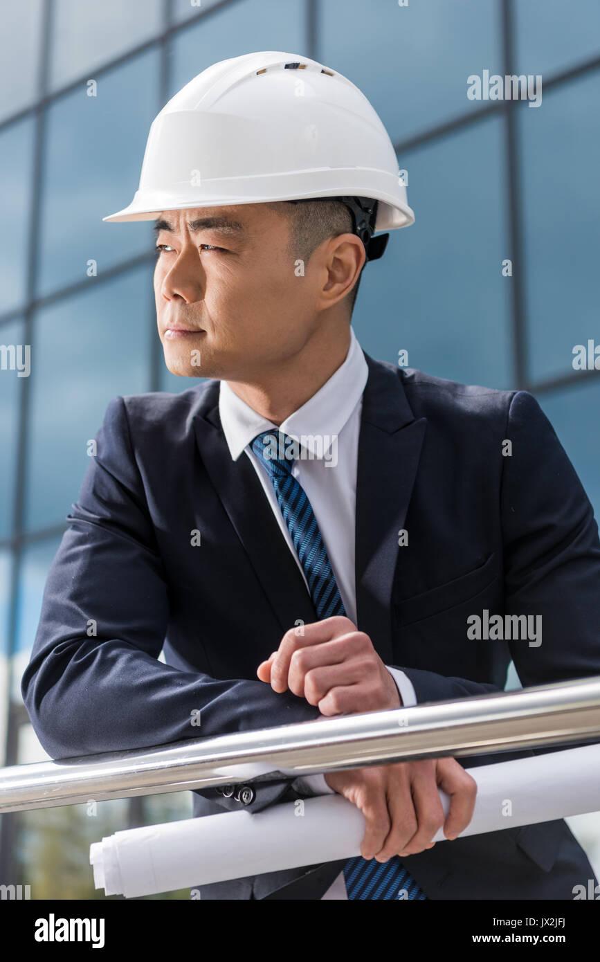 portrait of professional architect in hard hat holding blueprint - Stock Image