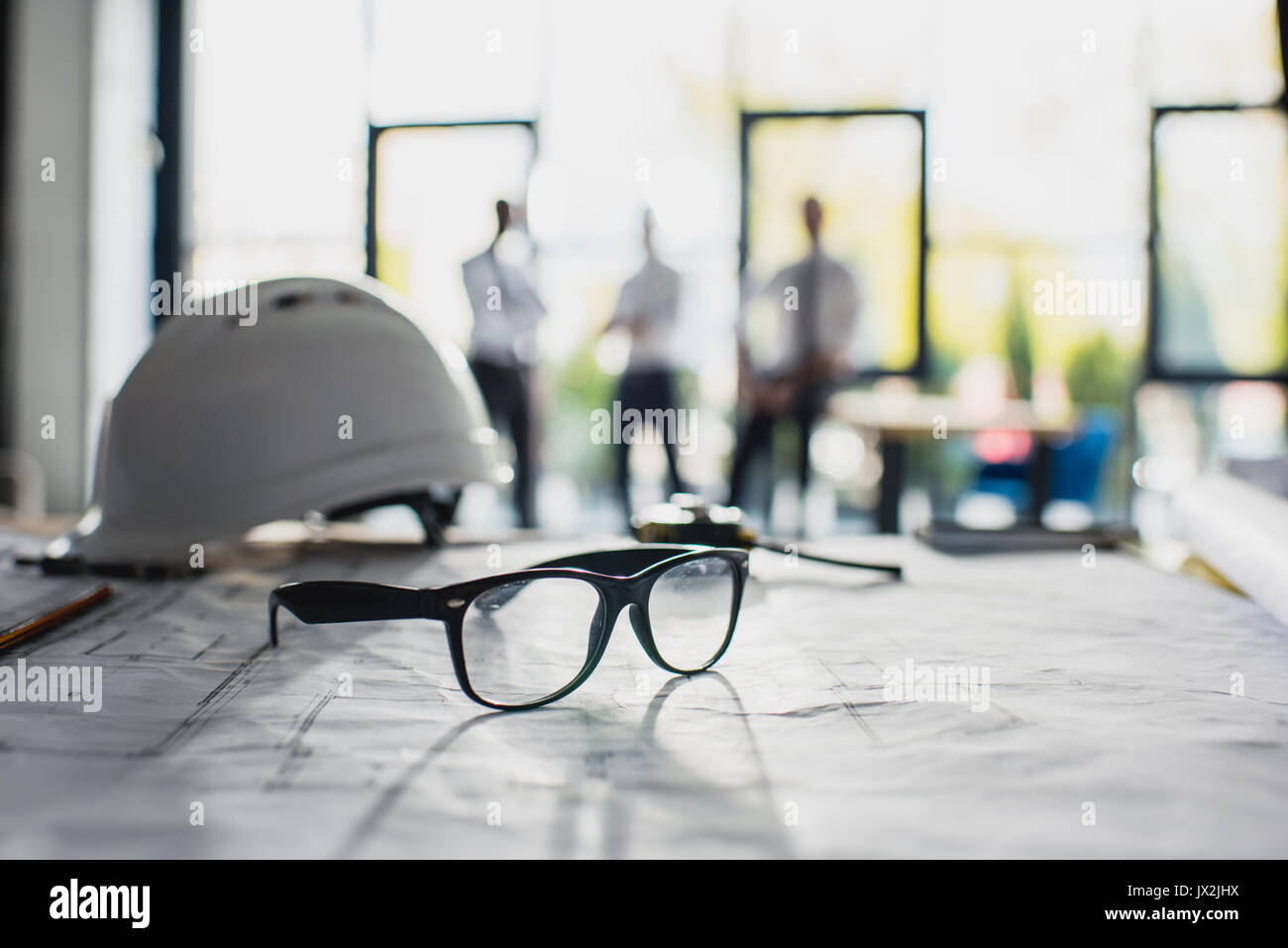 various architecture supplies on workplace with architects behind, focus on foreground  - Stock Image