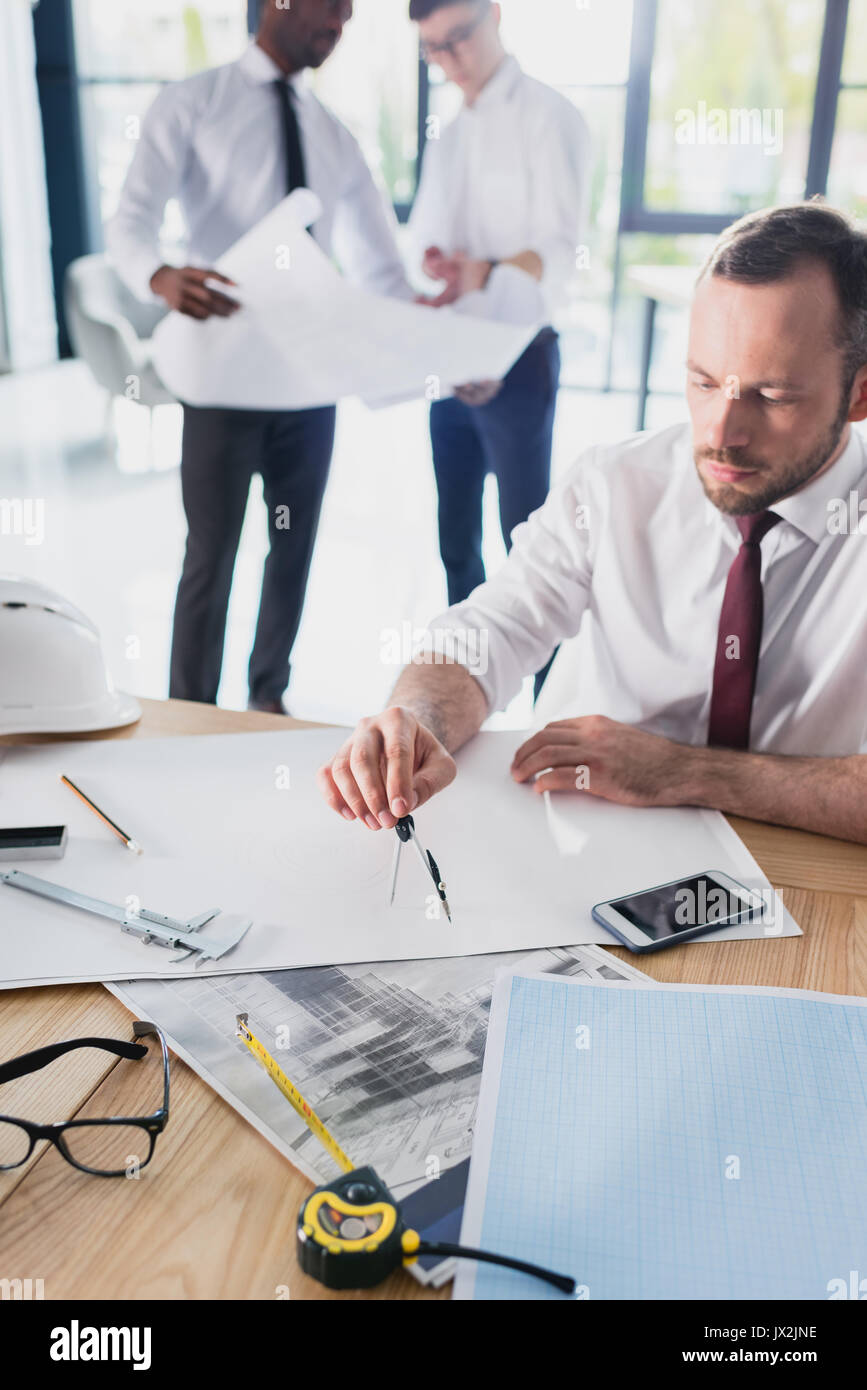 architect working on new project with colleagues behind in modern office - Stock Image