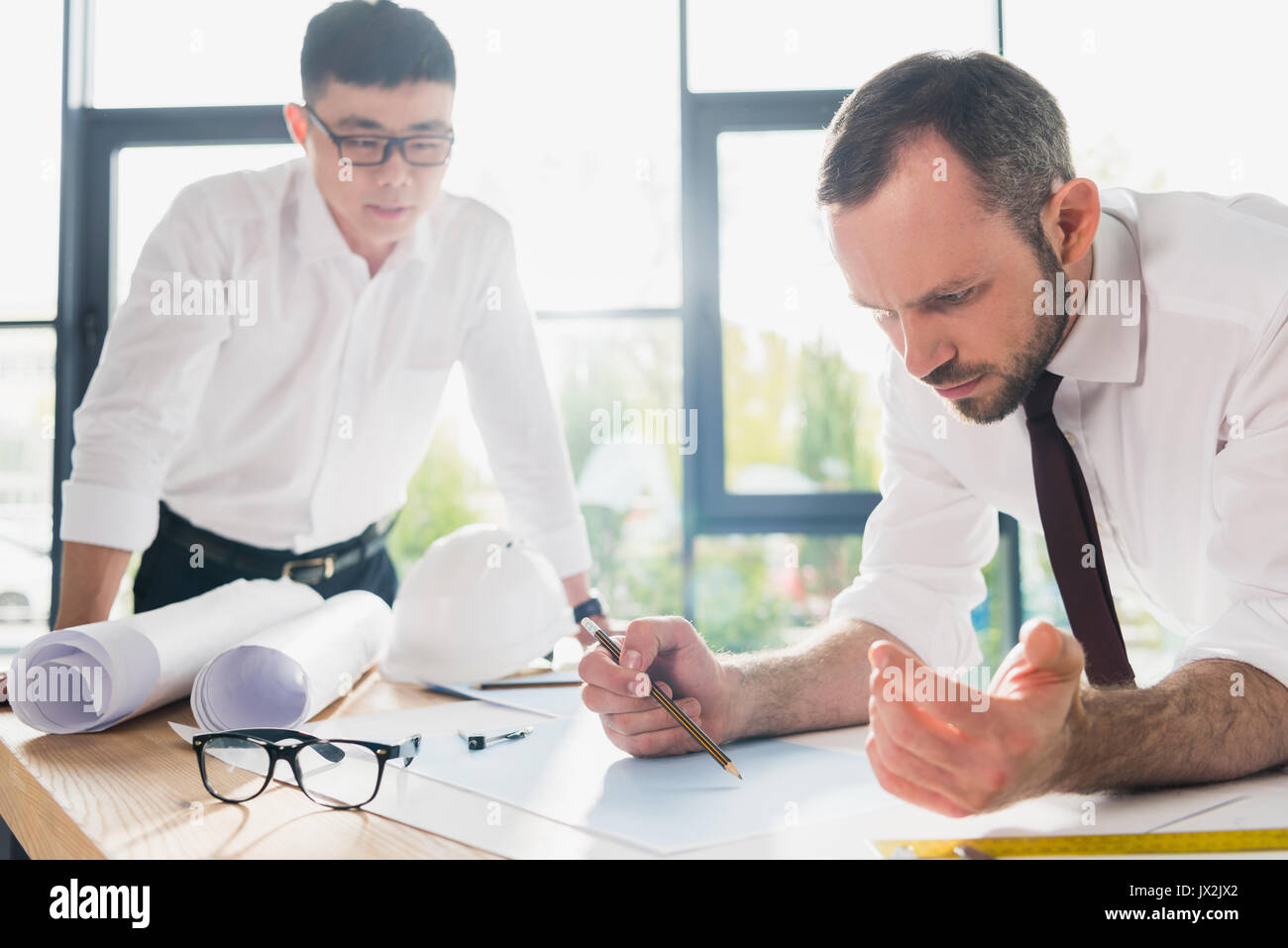 professional architects in formal wear working at modern office - Stock Image