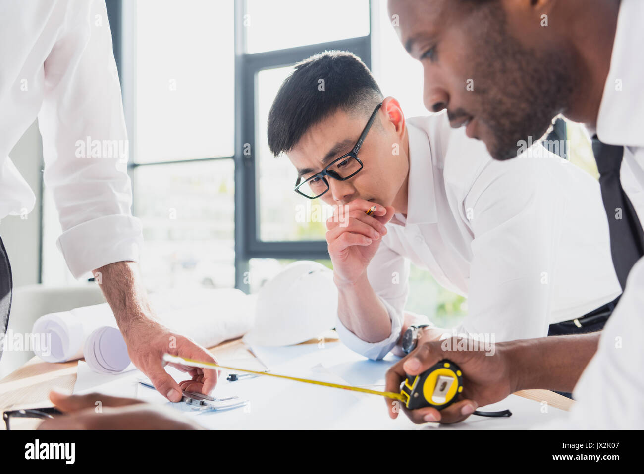 professional architects in formal wear working at modern office, businessmen group - Stock Image