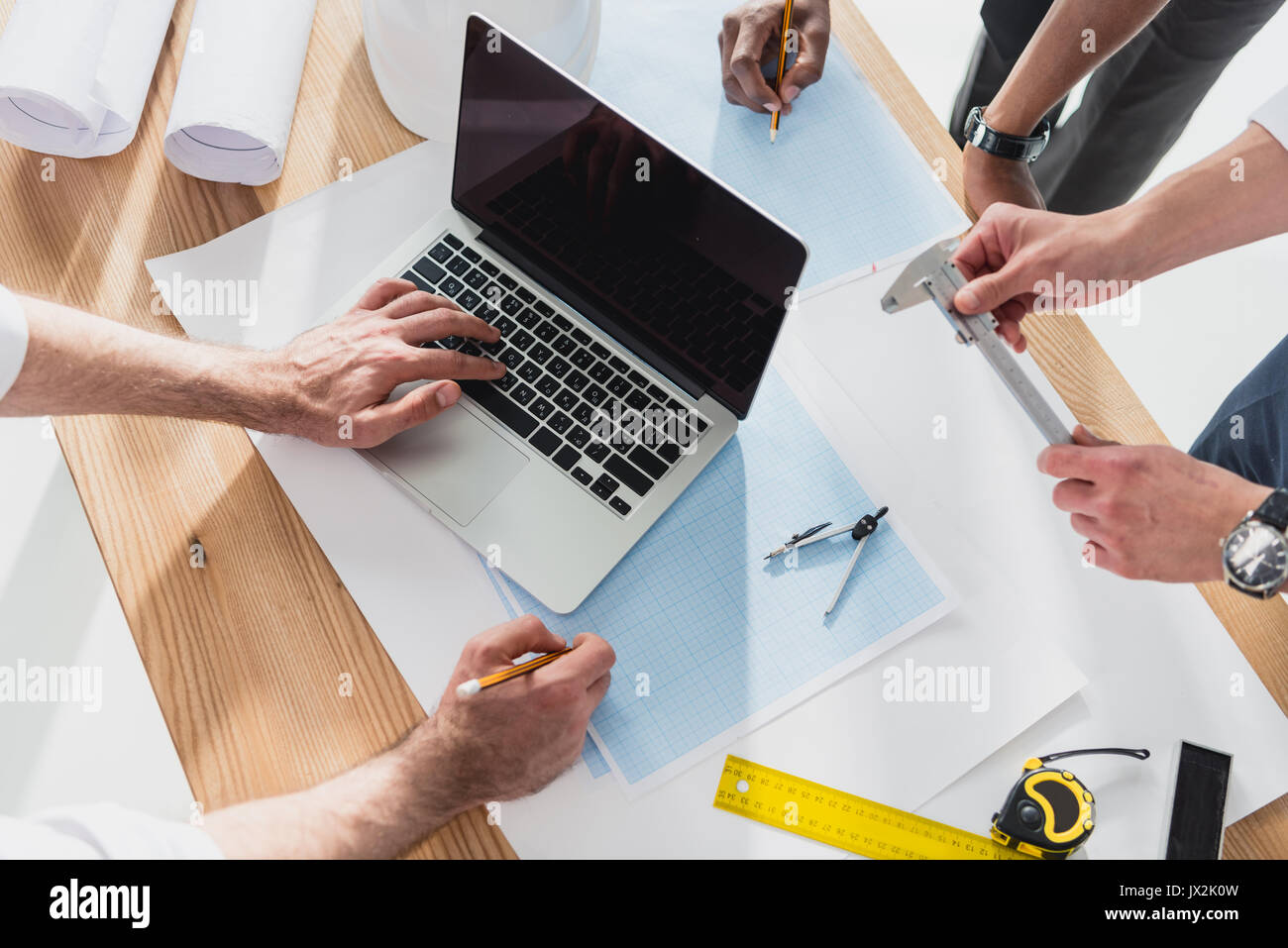 professional architects in formal wear working with laptop at modern office, businessmen group - Stock Image
