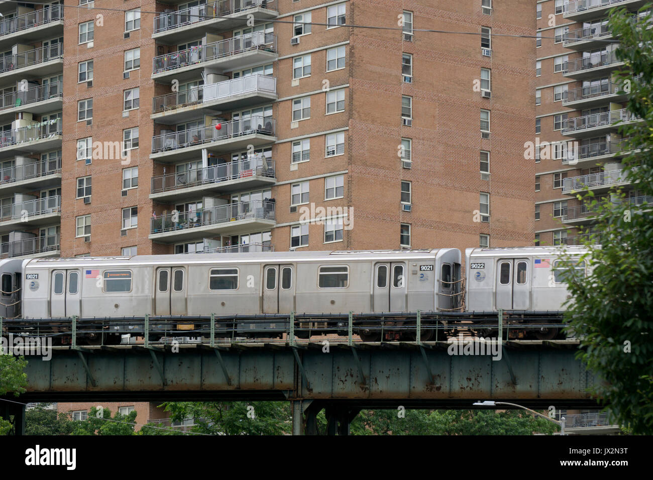 A noisy elevated New York City subway train passes several apartment houses in Brighton Beach Brooklyn, New York - Stock Image