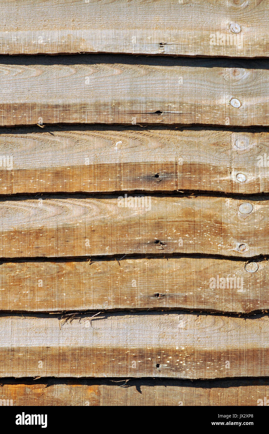 wooden garden fence or fencing panels in need of treating, treatment or painting with weatherproofing stain or paint. - Stock Image
