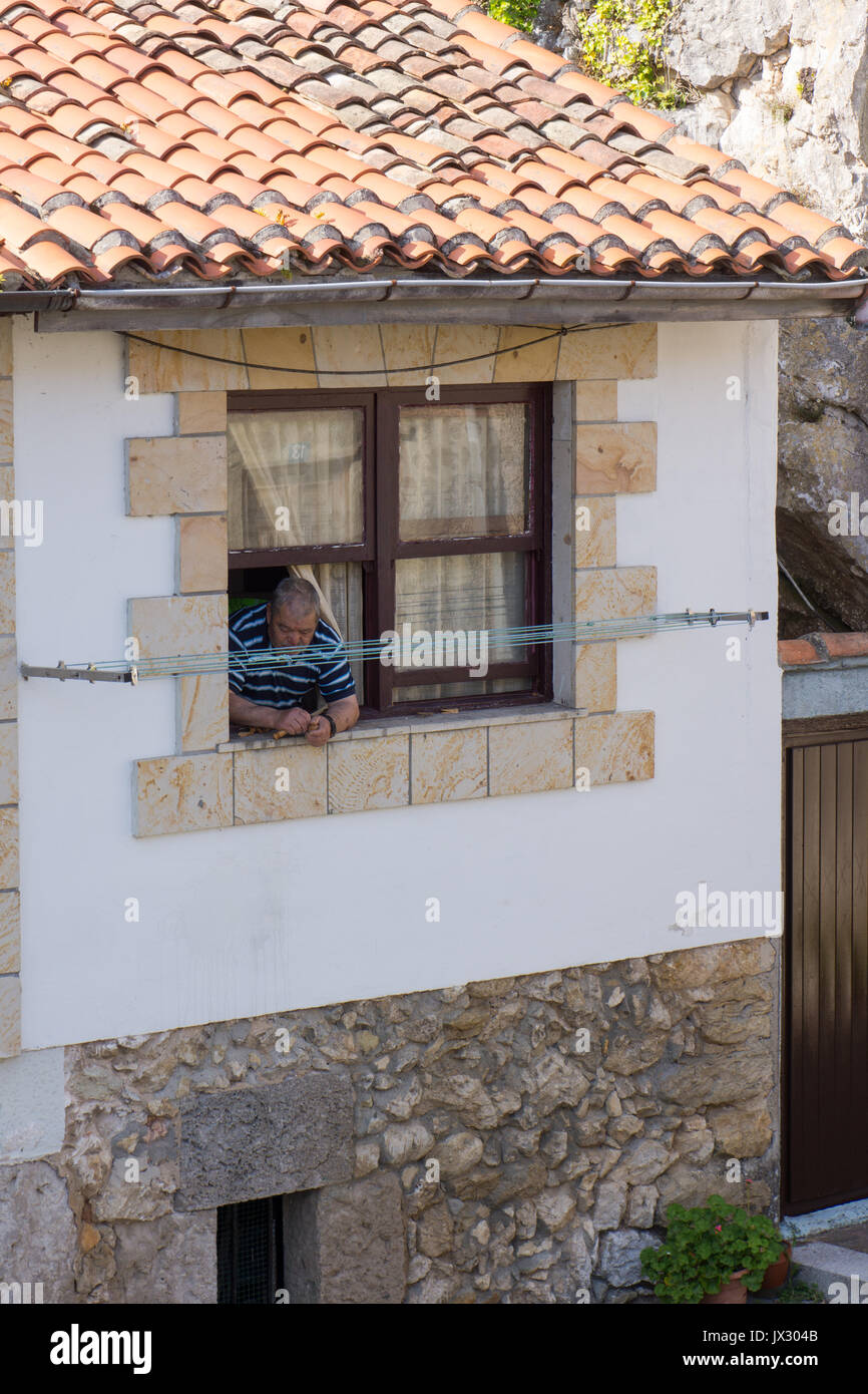 Older man leaning out of a window whilst breaking nuts in a town in northern Spain. - Stock Image
