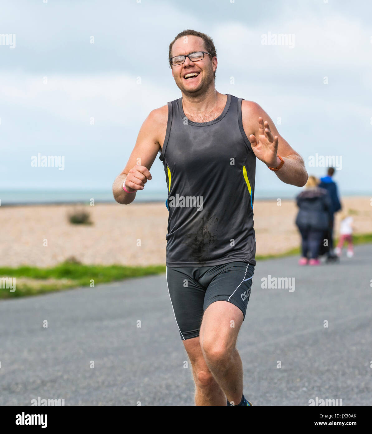 Man running as part of a running event along a seafront promenade. - Stock Image