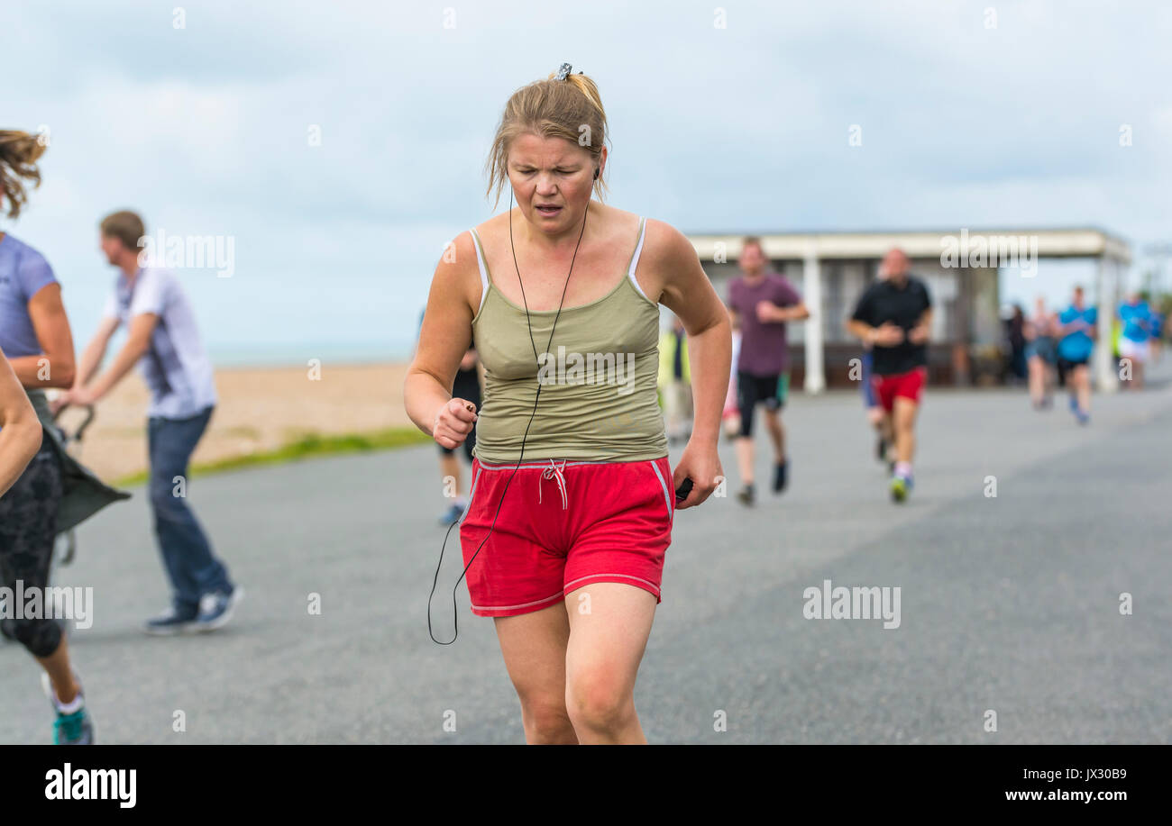 Young woman running on the weekly Vitality Parkrun event in Worthing, West Sussex, England, UK. - Stock Image