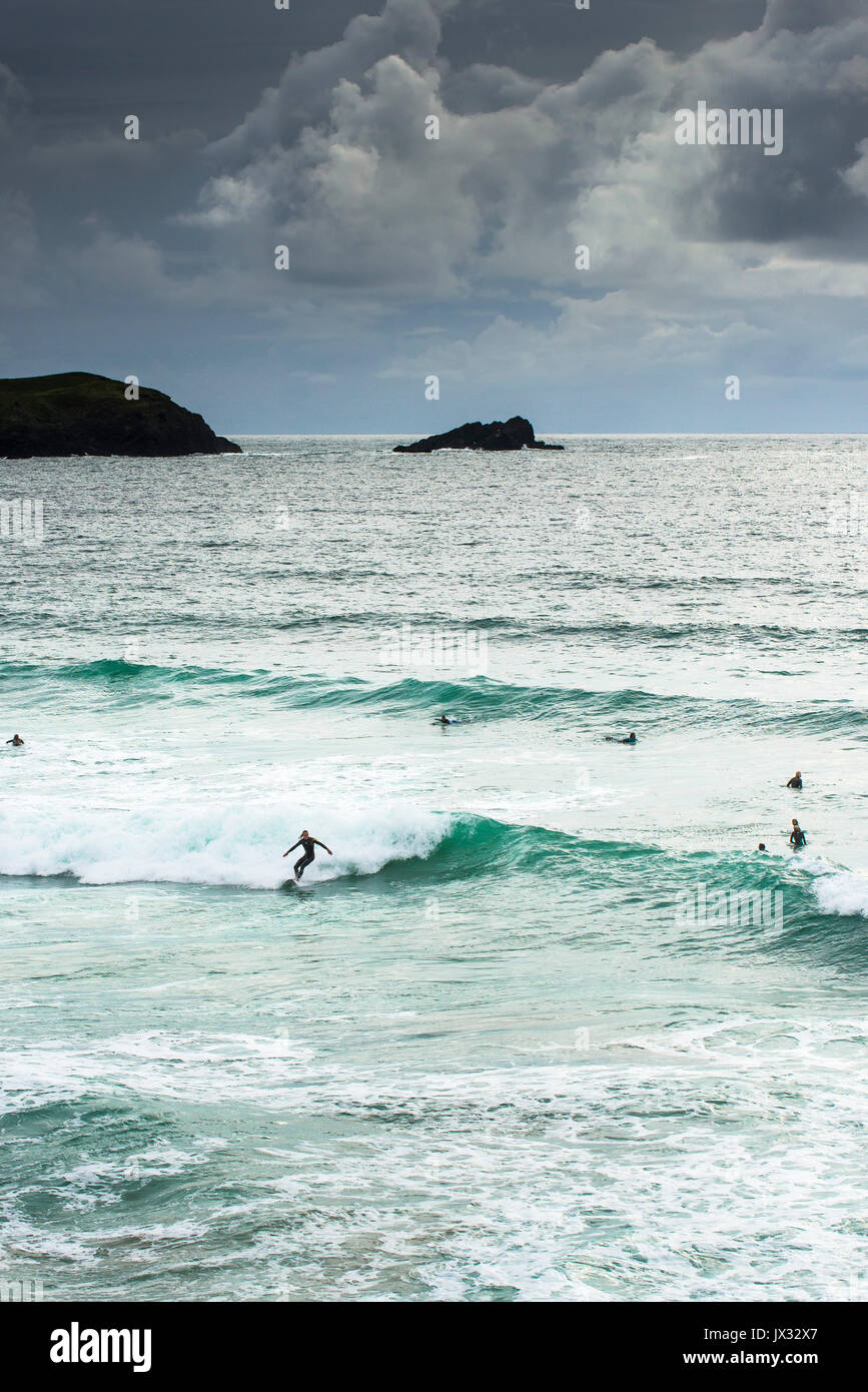 Surfing UK. A surfer riding a wave at Fistral as dark clouds gather. Newquay, Cornwall. - Stock Image