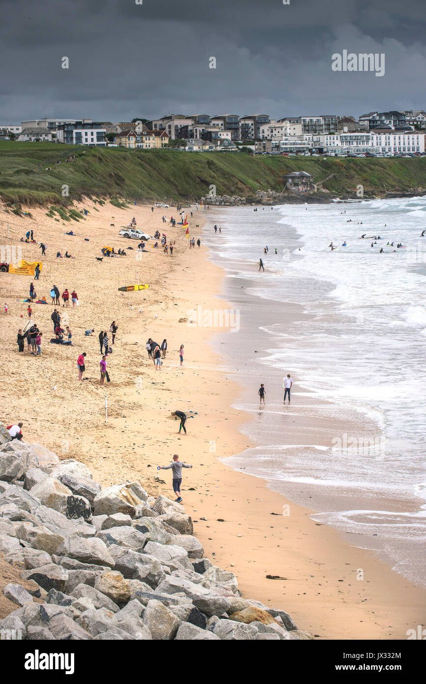 UK Weather.  Holidaymakers enjoying themselves on Fistral Beach despite dark clouds gathering. Stock Photo