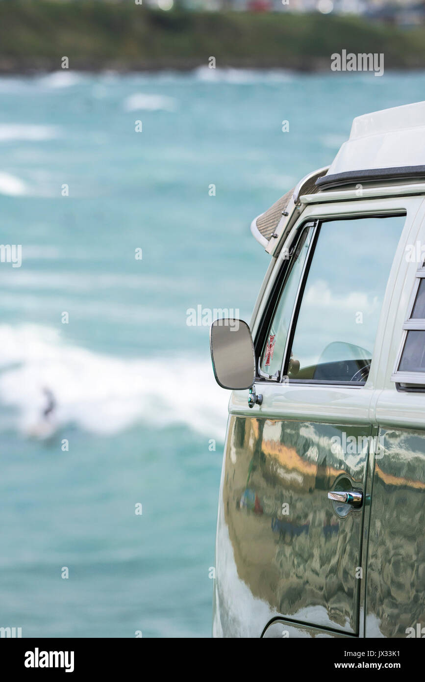 The wing mirror on the side of a vintage VW Campervan parked overlooking the sea. - Stock Image