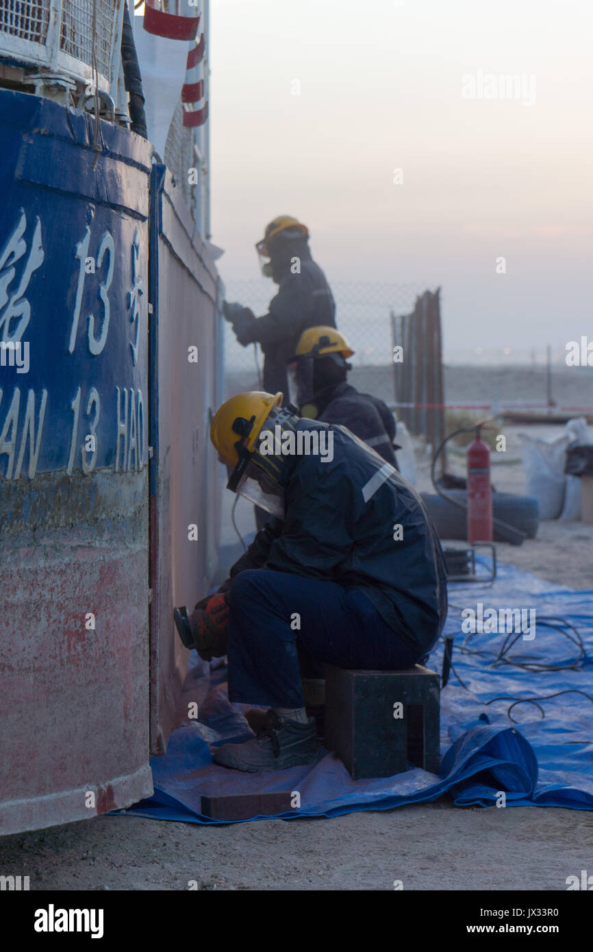 3 workers grinding with hand held angle grinders paint off the side of a hull of a boat in dry dock. - Stock Image