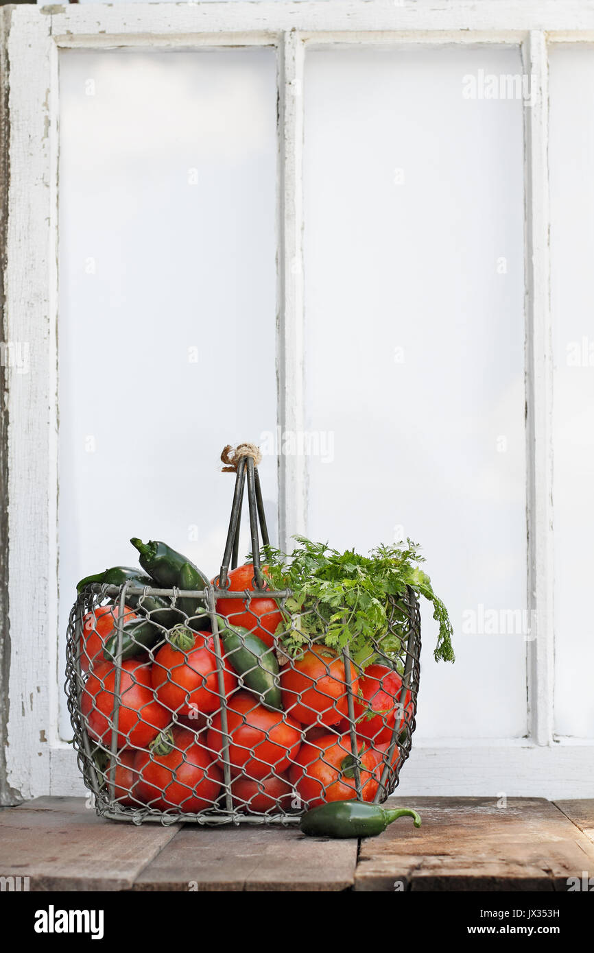 Ingredients for homemade salsa in an old country basket sitting in front of a window. - Stock Image