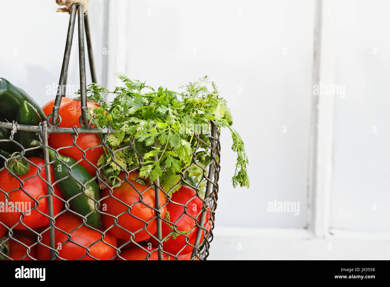 Ingredients for homemade salsa in an old country basket sitting in front of a window. Shallow depth of field. - Stock Image