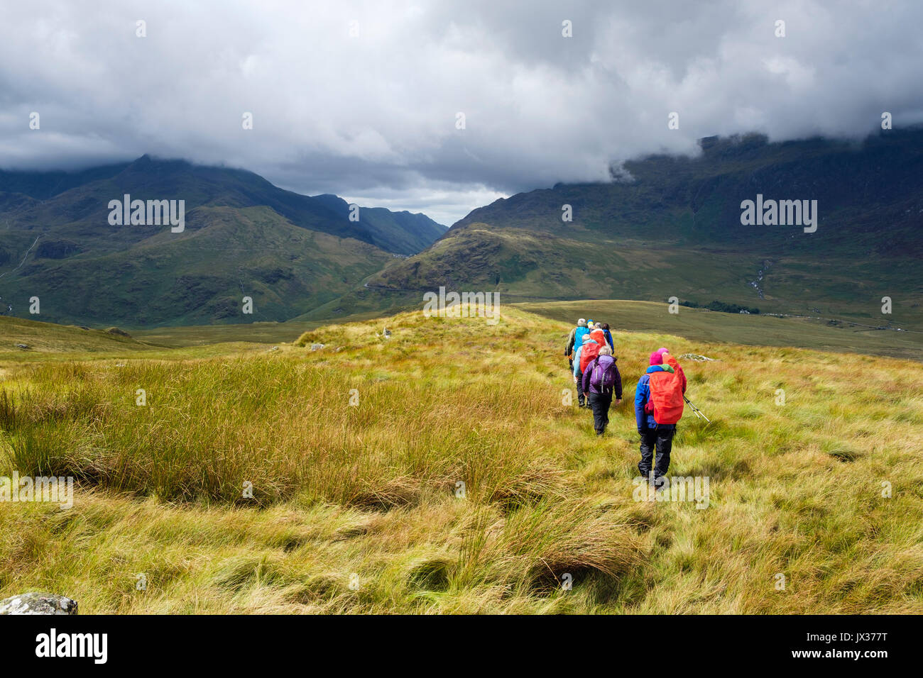 Ramblers group on Carnedd y Cribau hiking down to Pen Y Gwryd in sunshine following rain in mountains of Snowdonia Stock Photo