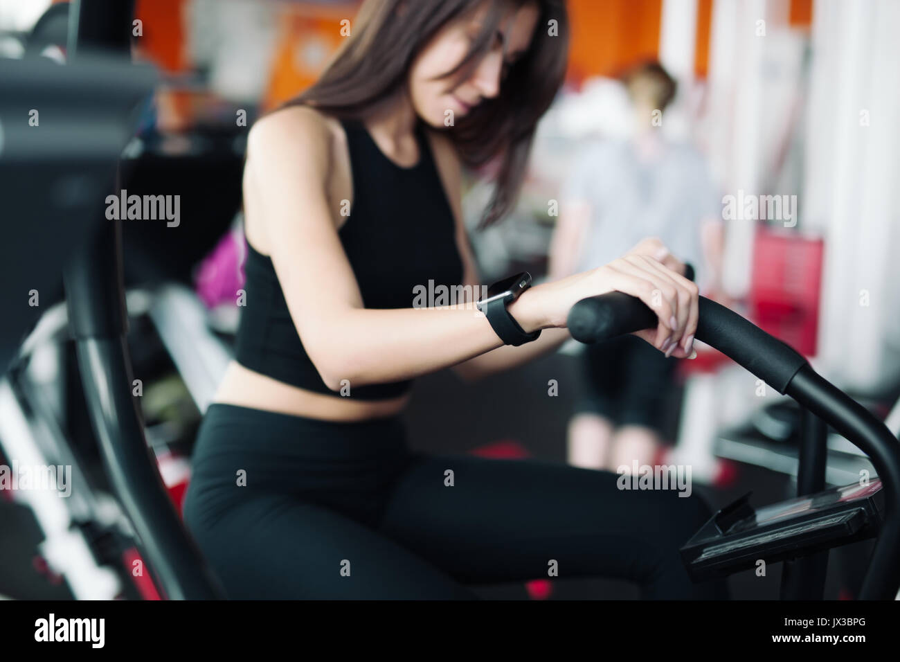 Woman 20s wearing smart watch working out on exercise bike 20s Stock