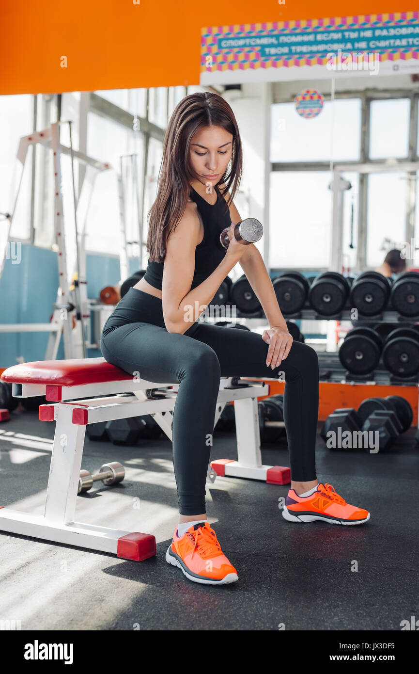 Fit young woman 20s doing shoulder raises with dumbbells in gym 20s - Stock Image