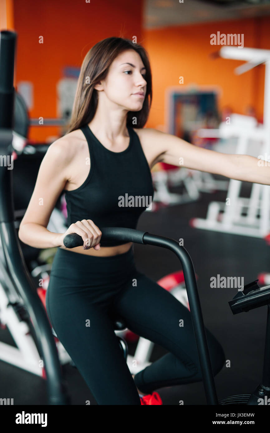 Woman 20s wearing smart watch working out on exercise bike 20s. - Stock Image