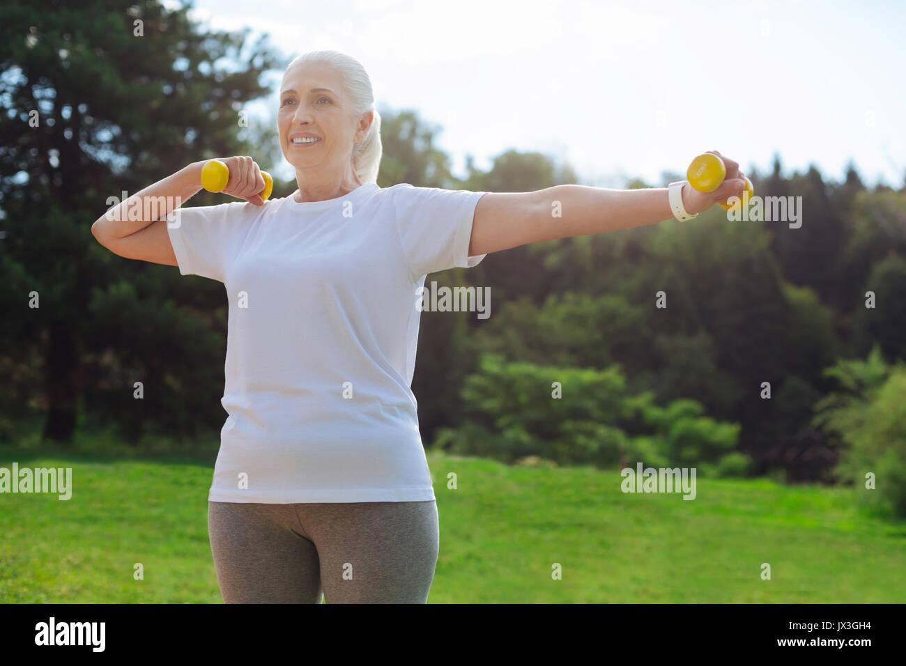 Healthy female using her dumbbells - Stock Image